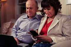 Two amused people playing with their devices Stock Image