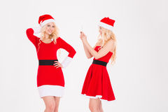 Two amusing beautiful sisters twins taking photos using cellphone Royalty Free Stock Photo