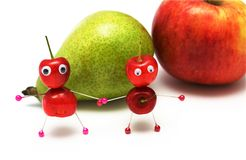 Two amusing little men from a sweet cherry. On a background of a pear and an apple royalty free stock images