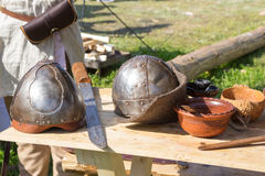 Two ancient helmet and sword on wooden table Stock Images