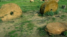 Two ancient millstones. The old millstones in the sand. Pan stock video