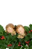 Two angel figurines on green holly leaves and red berries Stock Photos