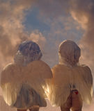 Two angels. Two angel decorations with sky background royalty free stock photography