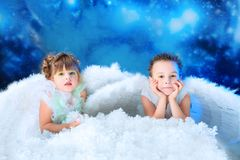 Two angels. Beautiful little angels at a snowy background Royalty Free Stock Images
