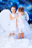 Two angels. Beautiful little angels at a snowy background Stock Photography