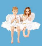 Two angels. Portrait of two cute angels sitting on the cloud Royalty Free Stock Photos