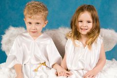 Two angels. Portrait of two cute children wearing white silk clothing and looking at camera Stock Photos