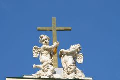 Two angels with a cross. Two angels with a cross, against the blue sky Royalty Free Stock Photo