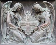 Two angels hold cross. Bas-relief on a cathedral in Saint-Petersburg. Two angels hold cross Stock Photography