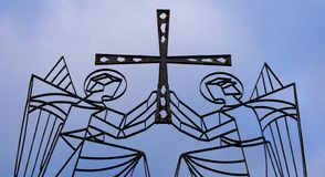 Two angels holding a cross. A photo of Two angels with wings holding a metal cross royalty free stock image