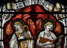 Two angels making music and singing. Stained glass window of 2 angels Royalty Free Stock Photos