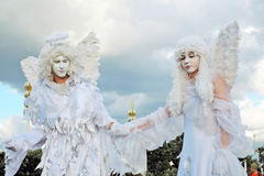 Two angels. MOSCOW - AUGUST 01, 2015: Street actors pose for photos in Moscow. They are dressed like angels. They walk on stilts. Inspiration open air festival Royalty Free Stock Photo