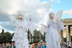 Two angels. MOSCOW - AUGUST 01, 2015: Street actors pose for photos in Moscow. They are dressed like angels. They walk on stilts. Inspiration open air festival Royalty Free Stock Images