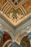 Two angels and other rich artwork decorating the ceiling. Detail of the richly ornamented ceiling with two angels on top of two arches, The Entrance Hall of The Royalty Free Stock Photography