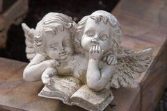Two angels reading a book. Dreaming and thinking about the world Stock Photo