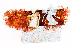 Two angels sitting on a box with tinsel. On a light background Royalty Free Stock Image