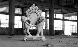 Two angels statuettes holding a broken clock. On the background of an abandoned building Stock Images