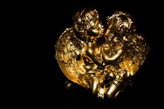 Gold cherubs angels with black background stock photography