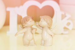 Two angels  with  wooden letters forming word LOVE Royalty Free Stock Photo