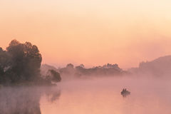 Two anglers on a boat enjoys fishing on a beautiful morning. stock photography