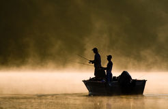 Two Anglers Fishing on A Lake. Two anglers fishing on a misty sunlit lake Royalty Free Stock Images