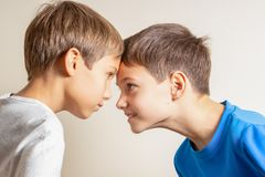 Two angry boys standing face to face, quarreling and looking at each other stock photo