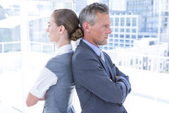 Two angry business colleagues standing back to back. In the office Royalty Free Stock Photography