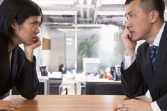 Two Angry Business people staring at each other across a table Stock Image
