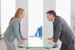 Two angry businesspeople arguing on each side of a desk Stock Image