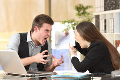 Two angry businesspeople arguing furious. Showing a negative growth graph at office Stock Images