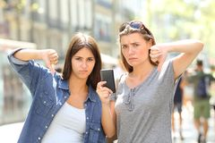 Two angry friends holding a phone with thumbs down. Two angry friends holding a smart phone with thumbs down in the street Stock Photography