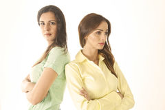 Two angry girls. Two upset and angry girl with arms crossed and backs to each other Stock Photography