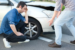 Two angry men arguing after a car crash. Two angry men arguing after a car fender-bender crash Royalty Free Stock Photos