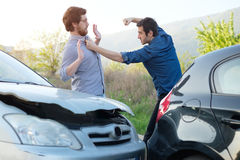 Two angry men arguing after a car crash Royalty Free Stock Image