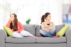 Two angry teenage girls sitting on sofa, at home, Royalty Free Stock Photos