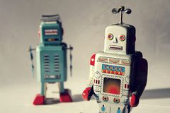 Two vintage tin toy robots, robotic delivery, artificial intelligence concept. Two angry vintage tin toy robots, artificial intelligence, robotic drone delivery Royalty Free Stock Photography