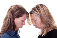 Two angry woman faces each other. Two pretty young women faces each other Royalty Free Stock Photos