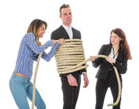 Two angry woman tying a business man with rope royalty free stock photo