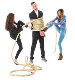 Two angry woman tying a business man with rope stock image