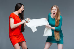 Two angry women quarreling and fighting for white dress Stock Photo