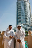 Two anonymous Arab men in traditional white clothing  looking at Stock Photography