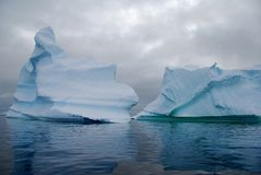 Two antarctic icebergs. Two icebergs in Antarctica, with dark sea Royalty Free Stock Image