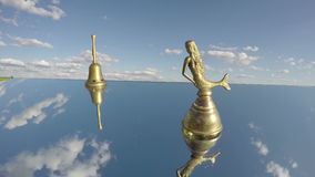 Two antique brass bells on mirror and clouds motion in wind. Timelapse 4K stock footage