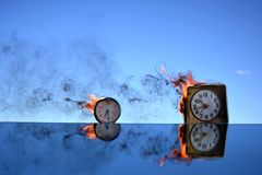 Two antique clock burning in space on mirror, time concept Stock Photos