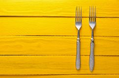 Two antique forks on a wooden table in yellow. Top view. Copy space Stock Photos