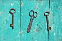 Two antique metal key and rusty scissors on wall Royalty Free Stock Image