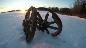 Two antique wooden wheels in the snow during sunset, time lapse 4K stock video footage