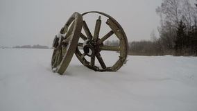 Two antique wooden wheels in the snow, time lapse 4K stock footage