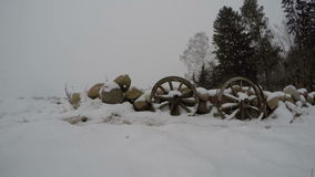 Two antique wooden wheels in the snow by the wall of stones, time lapse 4K stock video