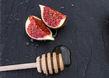 Two appetizing piece of fruit figs in honey and a wooden spoon on a black background. Two appetizing healthy sweet piece of fruit figs in honey and a wooden Royalty Free Stock Photography